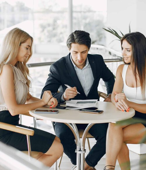 two women and a man sitting at a table| Stock Custodian